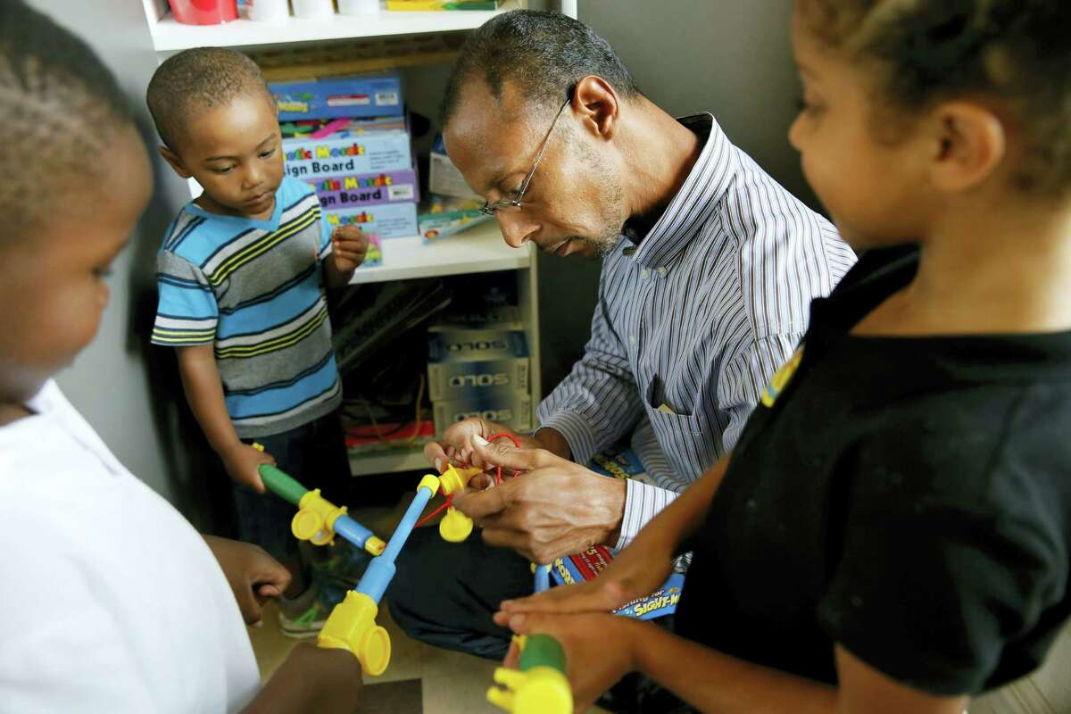 Miguel Moll untangles a set of toys for Jonah Smith, left, Moll's son Miguel Moll V, center, and and Victoria Carter, right, as he watches over them at an after school program at an apartment complex on Sept. 2, 2016 in Fort Worth, Texas. Miguel Moll knew the risk of rape when he was thrown into a Texas jail in 1989 after joyriding in a stolen car.