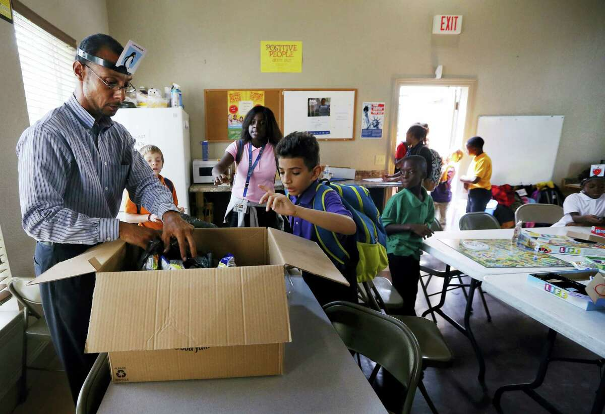Miguel Moll, left, hands out snacks to children arriving to an after school program at an apartment complex on Sept. 2, 2016 in Fort Worth, Texas. Moll knew the risk of rape when he was thrown into a Texas jail in 1989 after joyriding in a stolen car.