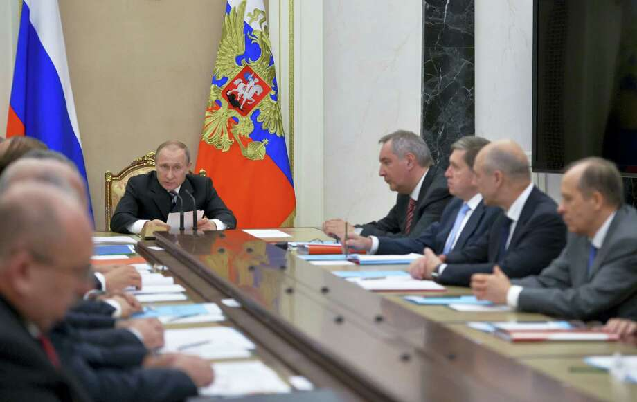 Russian President Vladimir Putin, back, leads a meeting with officials in Moscow, Russia, Friday. The meeting focused on Russia's arms trade and its military ties with other nations. Photo: The Associated Press  / POOL SPUTNIK KREMLIN