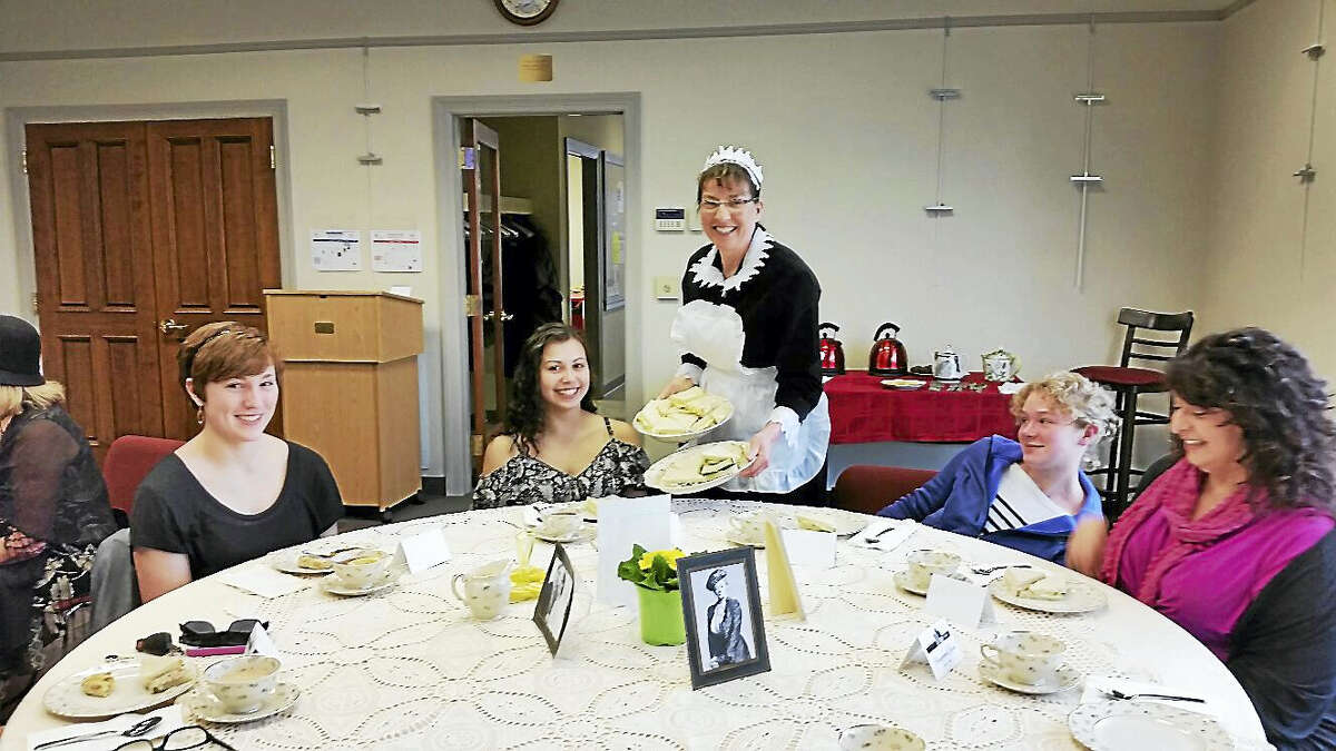 """Teen librarian Sara Lo Presti served Megan Porga, 16; Meghan Conlin, 16; Emily Porga, 14; and Lisa Conlin, all of Burlington, while dressed in a period costume at the """"Downton Abbey"""" Tea Party at the Burlington Public Library at 34 Library Lane in Burlington on Saturday afternoon."""
