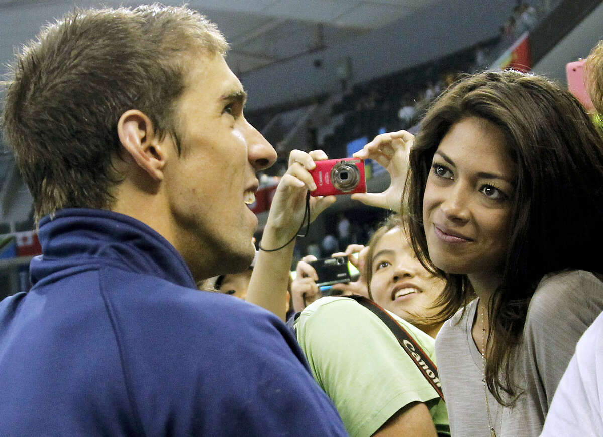 In this 2011 photo, U.S. swimmer Michael Phelps talks to his girlfriend Nicole Johnson. The couple welcomed Boomer Robert Phelps on Thursday night in Arizona, where Phelps has been training in preparation for the upcoming Rio Olympics.
