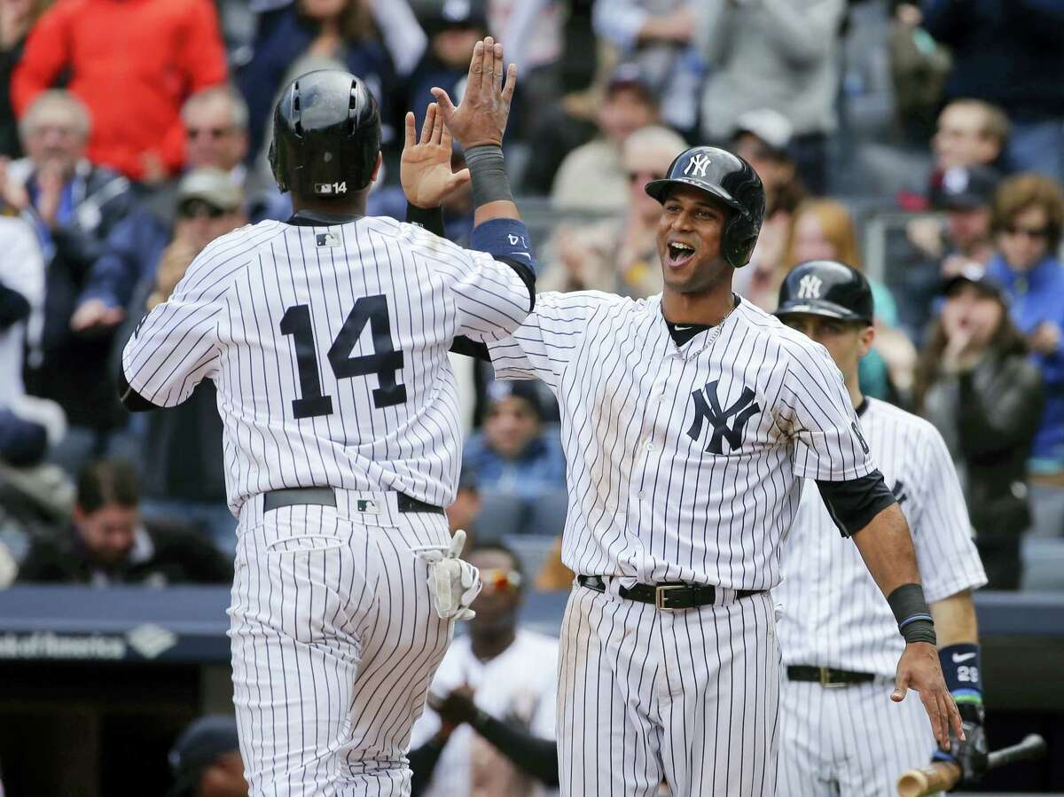 Aaron Hicks, right, celebrates with teammate Starlin Castro after they scored in the fifth inning against the Red Sox on Saturday.