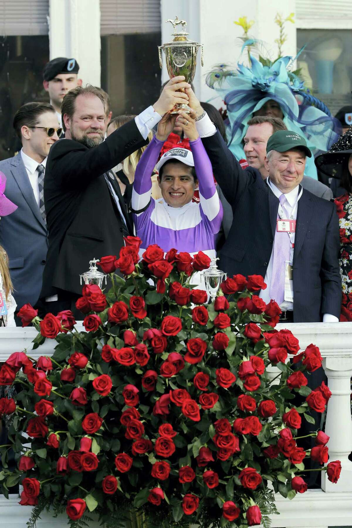 Mario Gutierrez, middle, trainer Doug O'Neill, left, and horse owner J. Paul Reddam hold the trophy after Gutierrez rode Nyquist to victory in the Kentucky Derby.