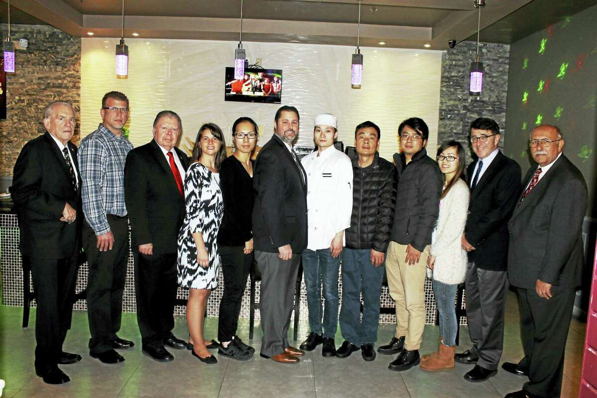 Kuyi Sushi Japanese restaurant in Cromwell held its grand opening in December. From left are: Chamber President Larry McHugh; co-chair, Cromwell Downtown Merchants Association Rodney Bitgood; Chairman, Cromwell Division Jay Polke; state Rep. Christie Carpino; owner Iris Wang; Mayor Enzo Faienza; sushi chef Kingsley Zheng; co-owner Xuezhong Yu; family members Jacob Li and Juanfang Yu; Planning Director Stuart B. Popper; and Town Manager Anthony J. Salvatore.