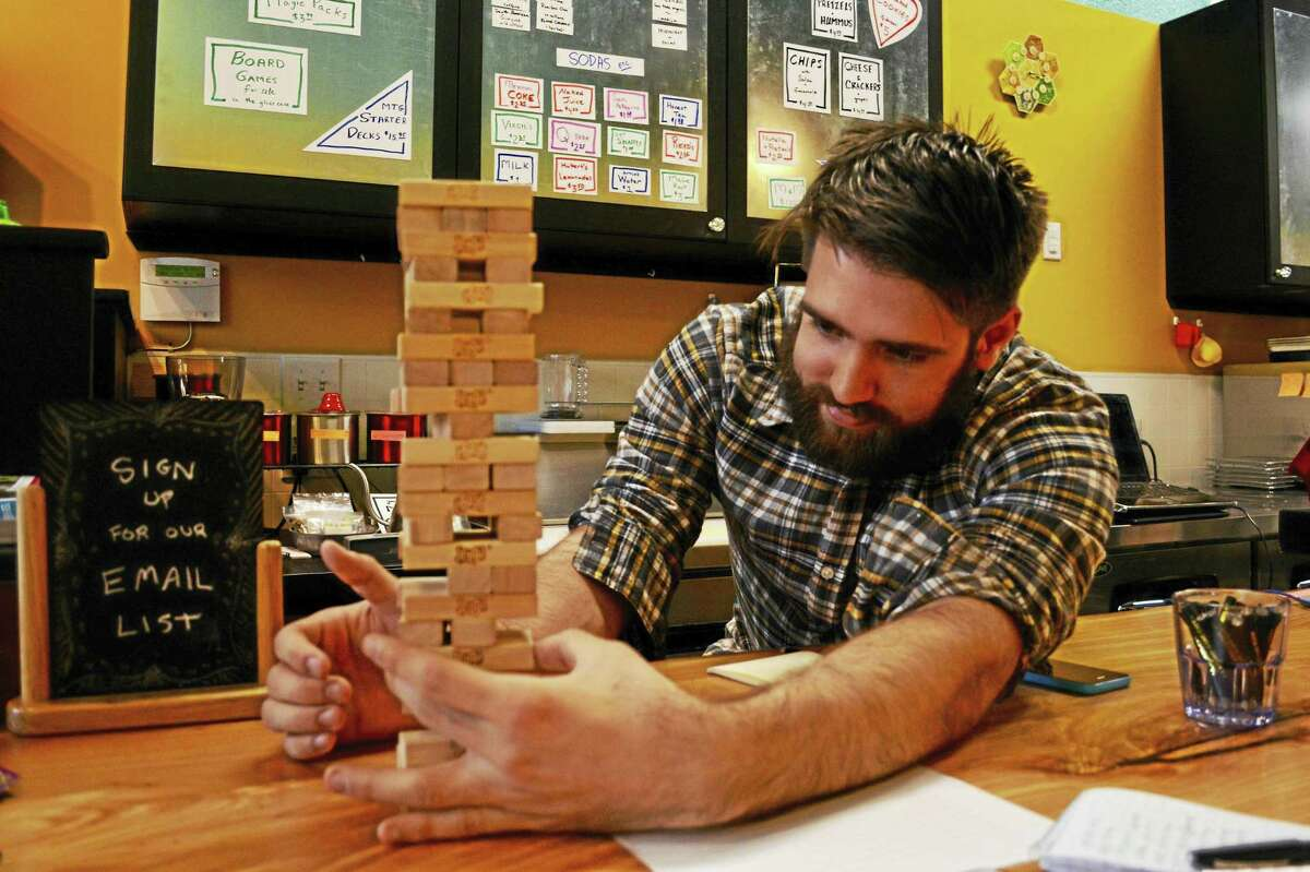 Tenzin Masselli, co-owner of Middletown's The Board Room cafe with his mother, Jen Alexander, builds a tower with Jenga pieces.