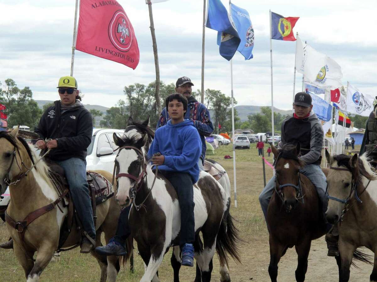 """Horseback riders make their way through an encampment near North Dakota's Standing Rock Sioux reservation on Sept. 9, 2016. The Standing Rock Sioux tribe's attempt to halt construction of an oil pipeline near its North Dakota reservation failed in federal court Friday, but three government agencies asked the pipeline company to """"voluntarily pause"""" work on a segment that tribal officials say holds sacred artifacts."""