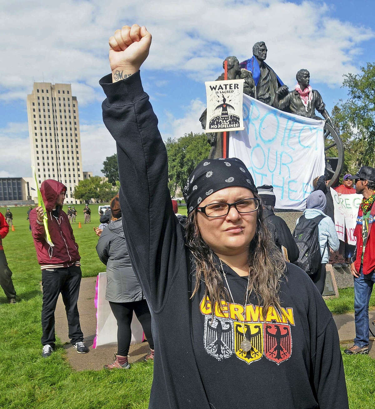 """Megan Tobin, of Bellevue, Ohio protests on the grounds of the North Dakota state capitol on Sept. 9, 2016 in Bismarck, N.D. The federal government stepped into the fight over the Dakota Access oil pipeline Friday, ordering work to stop on one segment of the project in North Dakota and asking the Texas-based company building it to """"voluntarily pause"""" action on a wider span that an American Indian tribe says holds sacred artifacts."""