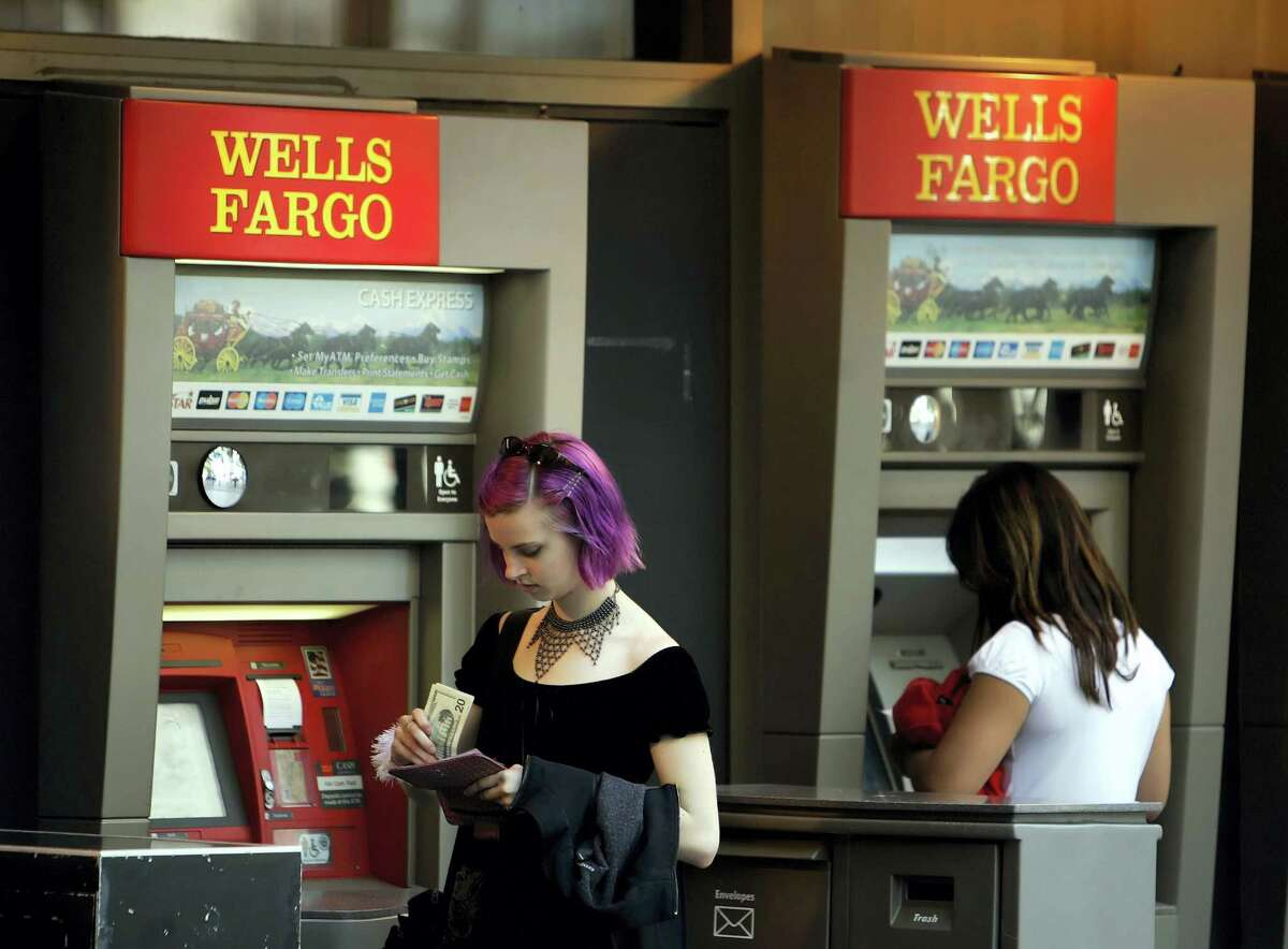 A woman puts away her money after visiting a Wells Fargo automated teller machine in San Francisco.