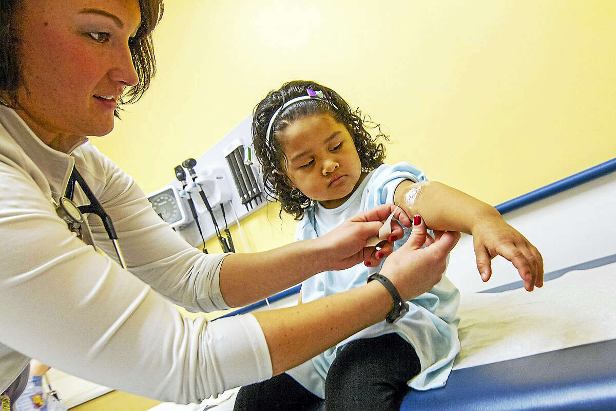 Three-year-old Angely Nunez, watches as nurse Lauren Frazer applies a topical anesthetic to Angely's arm before a blood draw to check for levels of lead in her bloodstream at Connecticut Children's Primary Care Center in Hartford. Tests revealed elevated levels of lead in Angely's blood and she began treatment with Dr. Hilda Slivka at the center.