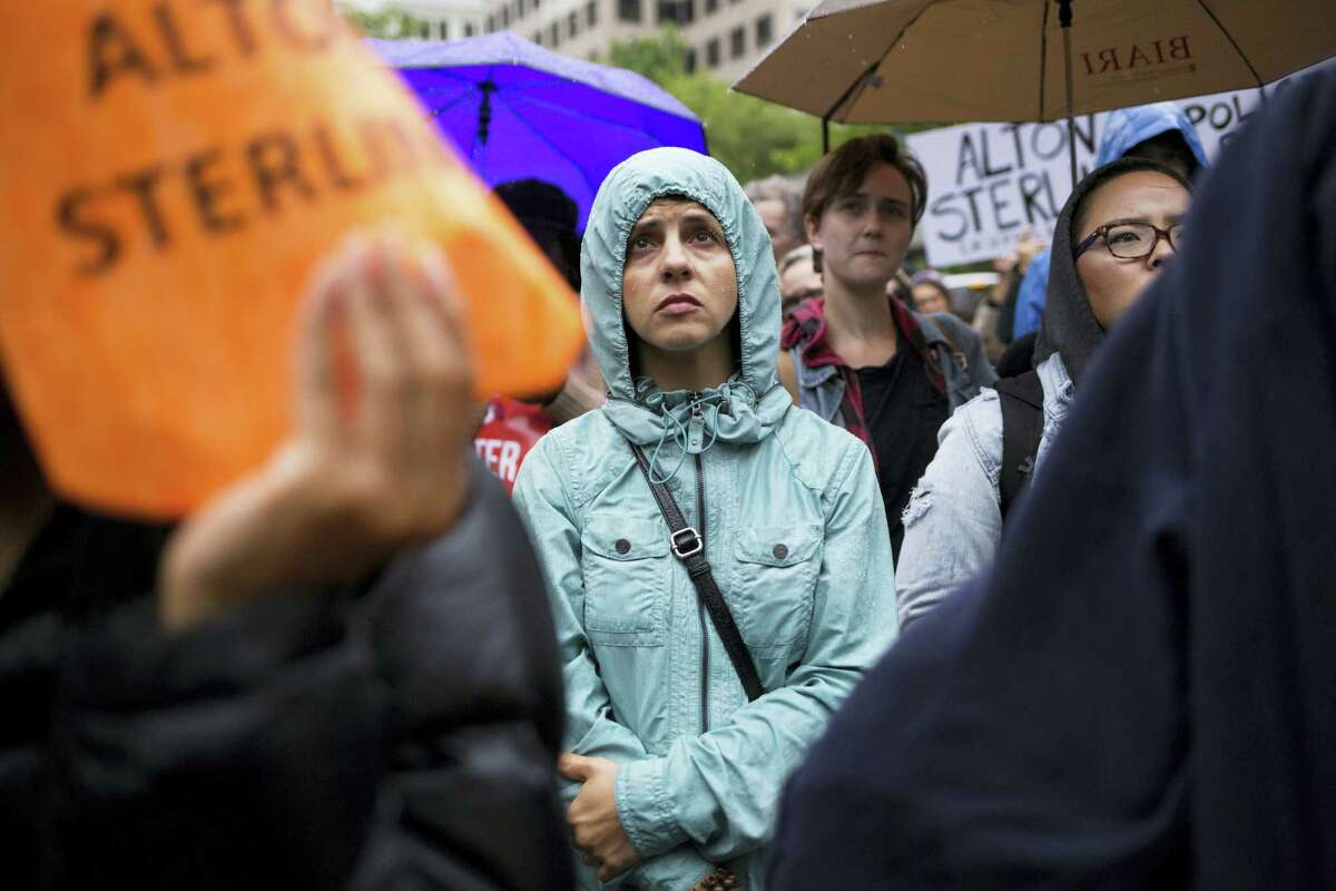 Protesters listen to speakers at Westlake Park during a rally Thursday in Seattle. Hundreds of people marched through downtown Seattle to protest the police-related shootings of two black men in Louisiana and Minnesota.