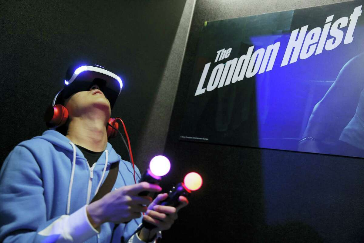 """A video game enthusiast experiences the Playstation VR virtual reality headset with the game """"The London Heist"""" at the Taipei Game Show 2016 in Taipei, Taiwan."""