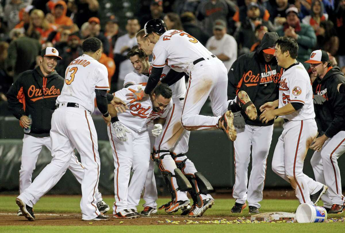 Members of the Baltimore Orioles celebrate with designated hitter Pedro Alvarez, third from left, after he hit a sacrifice fly ball in the 10th inning to defeat the Yankees 1-0