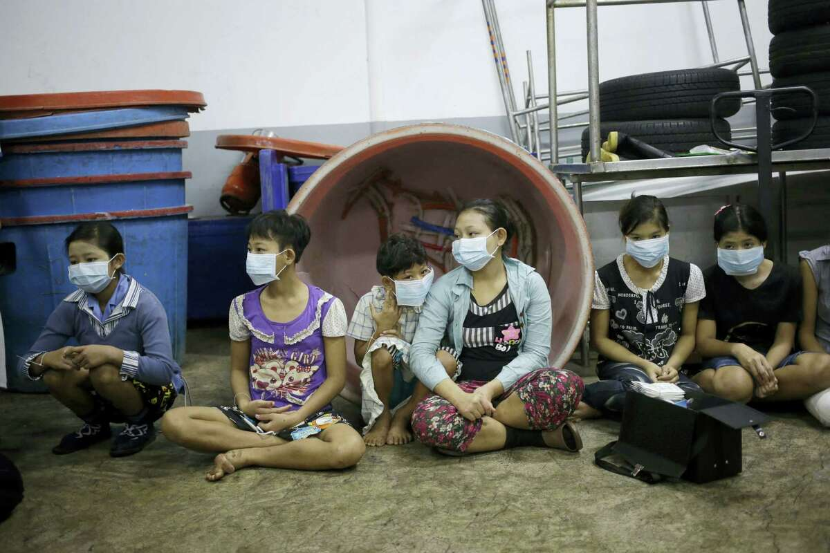 In this Nov. 9, 2015, photo, children sit together to be registered by officials during a raid on a shrimp shed in Samut Sakhon, Thailand. Abuse is common in Samut Sakhon, which attracts workers from some of the world's poorest countries, mostly from Myanmar. An International Labor Organization report estimated 10,000 migrant children aged 13 to 15 work in the city. Another U.N. agency study found nearly 60 percent of Burmese laborers toiling in its seafood processing industry were victims of forced labor.