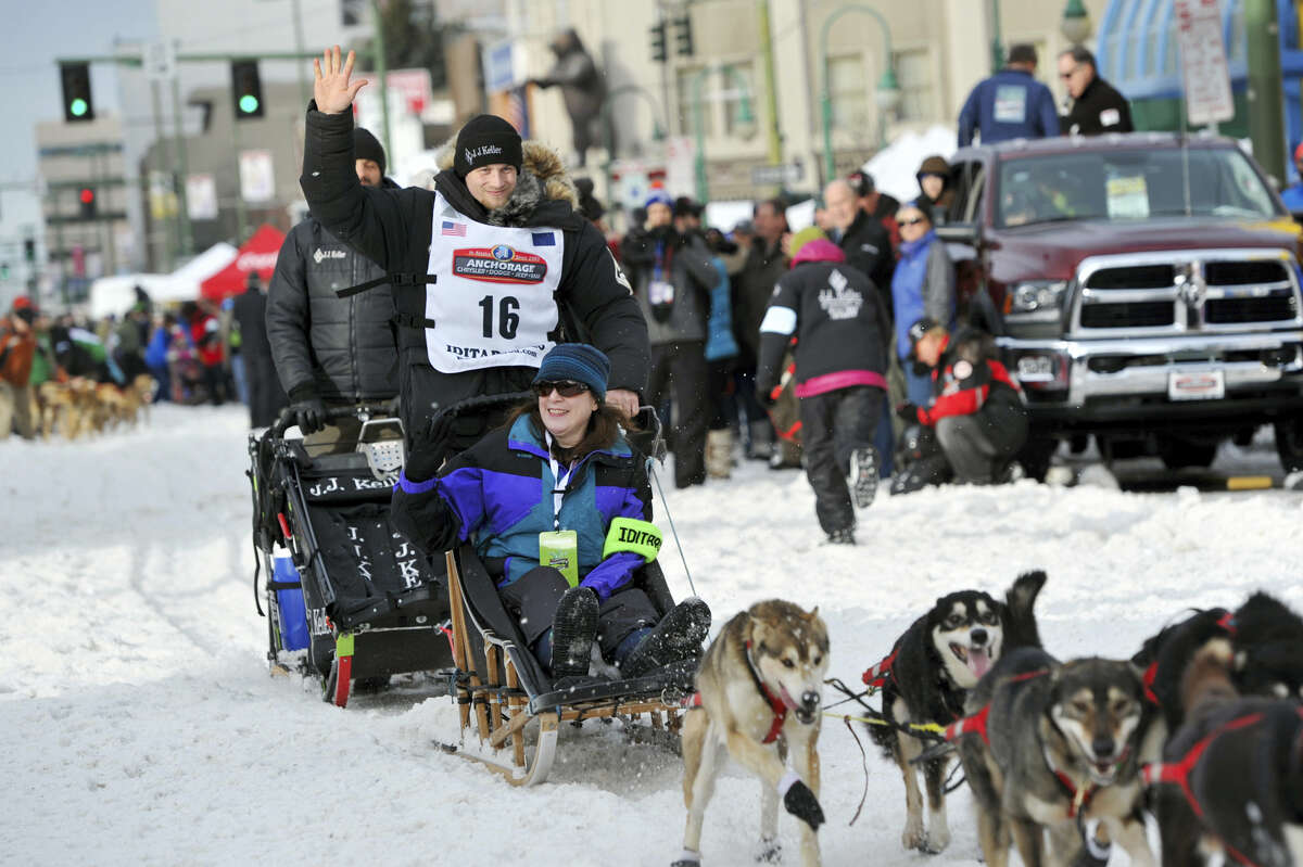 Defending Iditarod Trail Sled Dog Race champion Dallas Seavey (16) waves to the crowd as she begins the ceremonial start of the 1,000-mile race in Anchorage, Alaska on March 5, 2016.