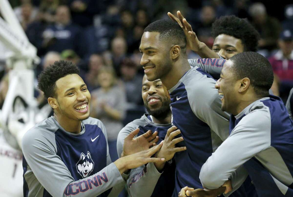 UConn's Jalen Adams (at left, front row), Sam Cassell Jr., Phillip Nolan, and Rodney Purvis, celebrate as Nolan walks on to the court during Senior Day ceremonies before the Huskies defeated UFC Sunday.