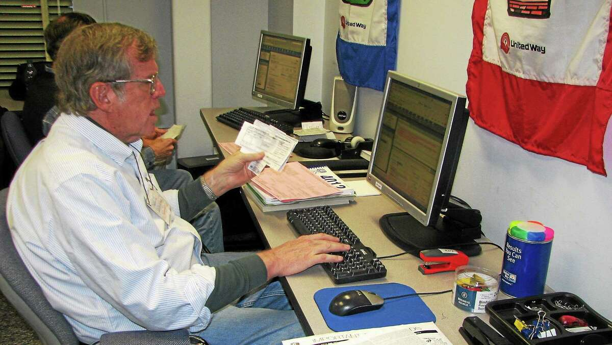 Volunteer David Morgan assists a client with taxes at the VITA site at the Middlesex United Way office in Middletown.