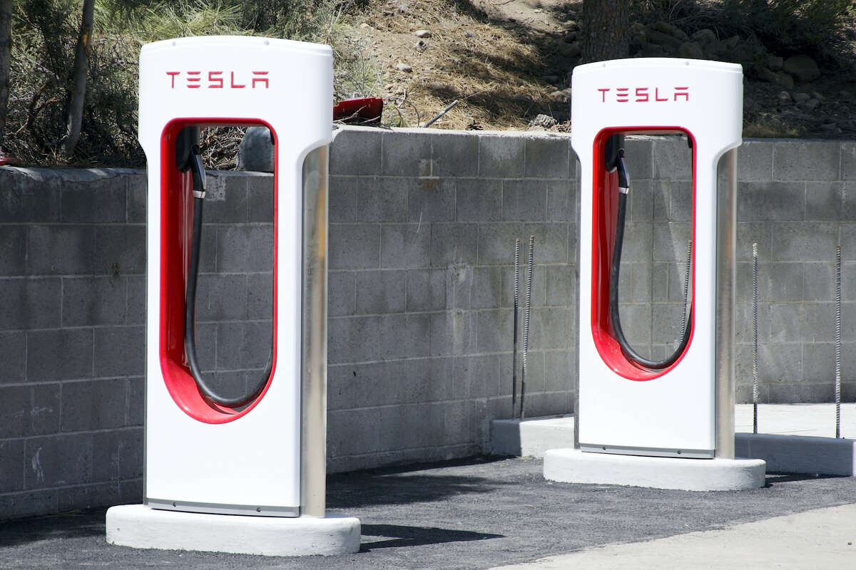This undated file photo shows Tesla Motors charging stations neat Truckee, Calif. Electric car maker Tesla Motors says it will end free use of its worldwide charging station network. The company says cars ordered after Jan. 1, 2017 will get roughly 1,000 miles worth of credits at the supercharging stations. After credits are used, owners will have to pay fees. Cars ordered or sold on or before Jan. 1 would still get free charging.