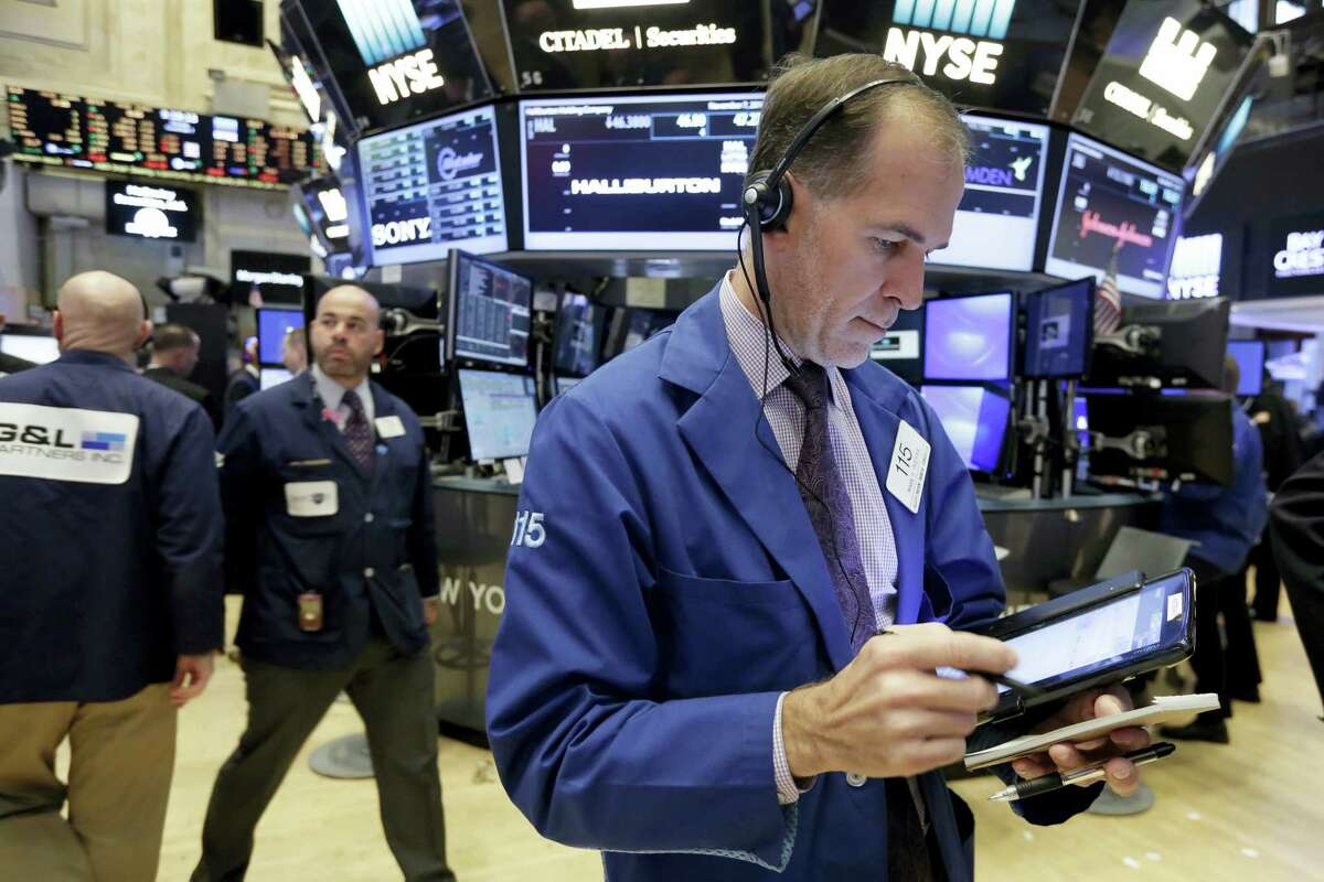 Trader Mark Puetzer, right, works on the floor of the New York Stock Exchange Monday.