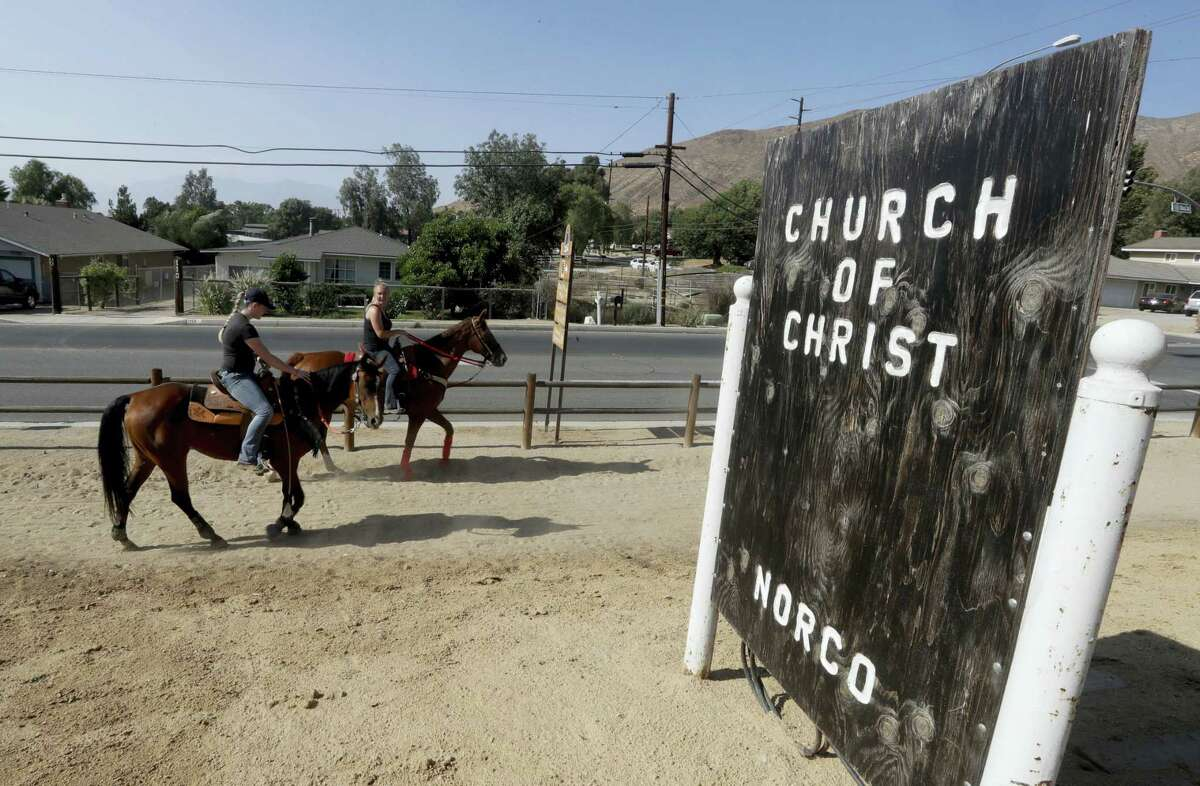 Two women on horseback ride near downtown Norco. The Southern California city has rejected plans for a proposed Hindu cultural center partly because officials say the large, domed building doesn't fit in with its Old West-style motif.