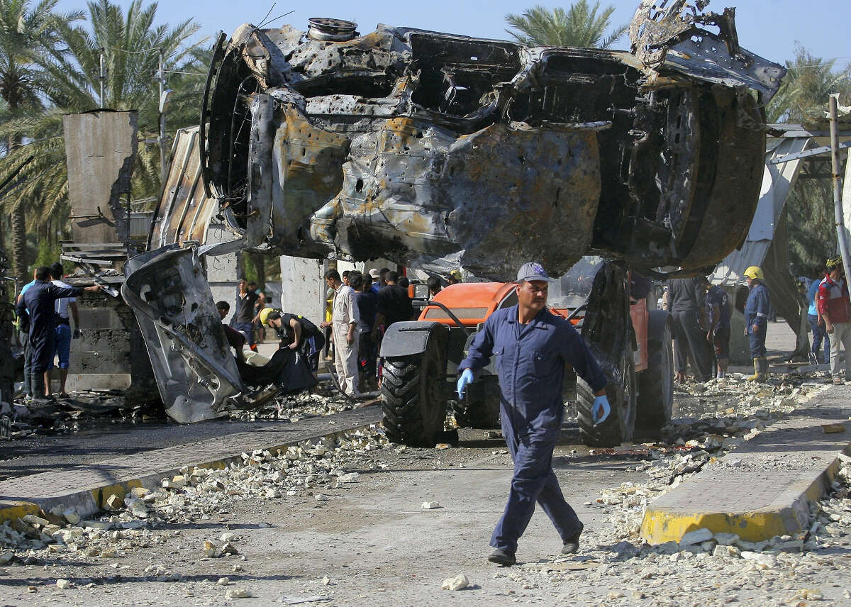Civilians and security forces gather as municipality workers remove destroyed vehicles at the scene of a deadly suicide bomb attack in Hillah, about 60 miles (95 kilometers) south of Baghdad, Iraq on March 6, 2016. The suicide bomber rammed his explosives-laden fuel truck into a security checkpoint south of Baghdad, killing and wounding dozens, officials said, the latest episode in an uptick in violence in the war-ravaged country.