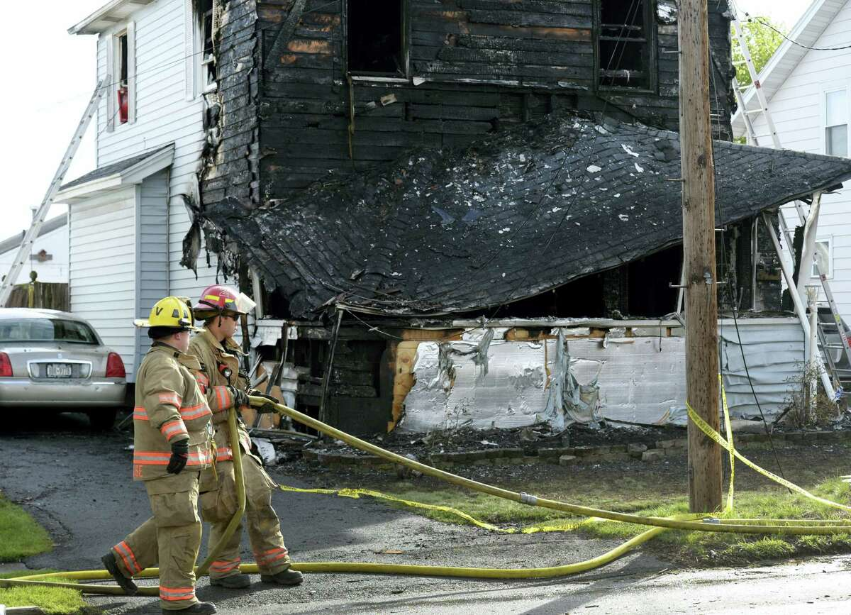 Syracuse firefighters begin to clean up at the scene of a fatal fire, Friday May 6, 2016, in Syracuse, N.Y. The blaze was reported early Friday morning. When firefighters arrived just minutes after receiving a 911 call, the front of the house was engulfed in flames, officials said.