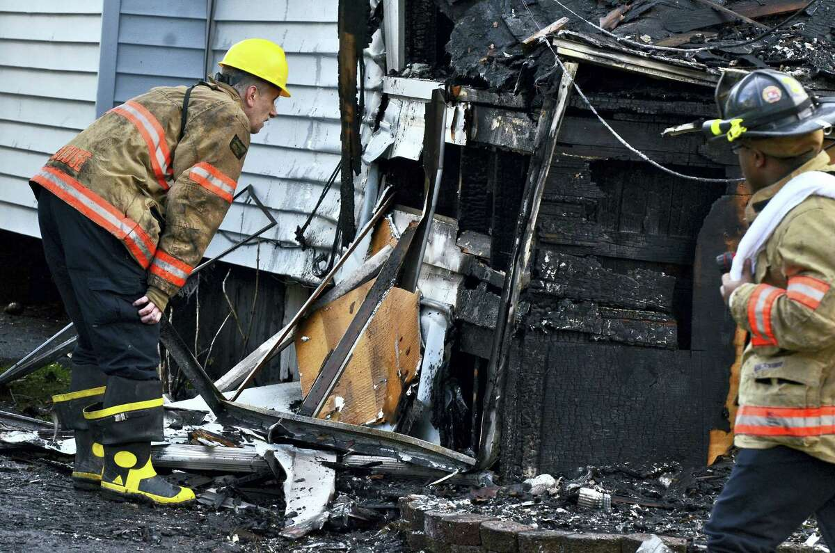 Syracuse firefighters look at the burnt structure at the scene of a fatal fire, Friday May 6, 2016, in Syracuse, N.Y. The blaze was reported early Friday morning. When firefighters arrived just minutes after receiving a 911 call, the front of the house was engulfed in flames, officials said.