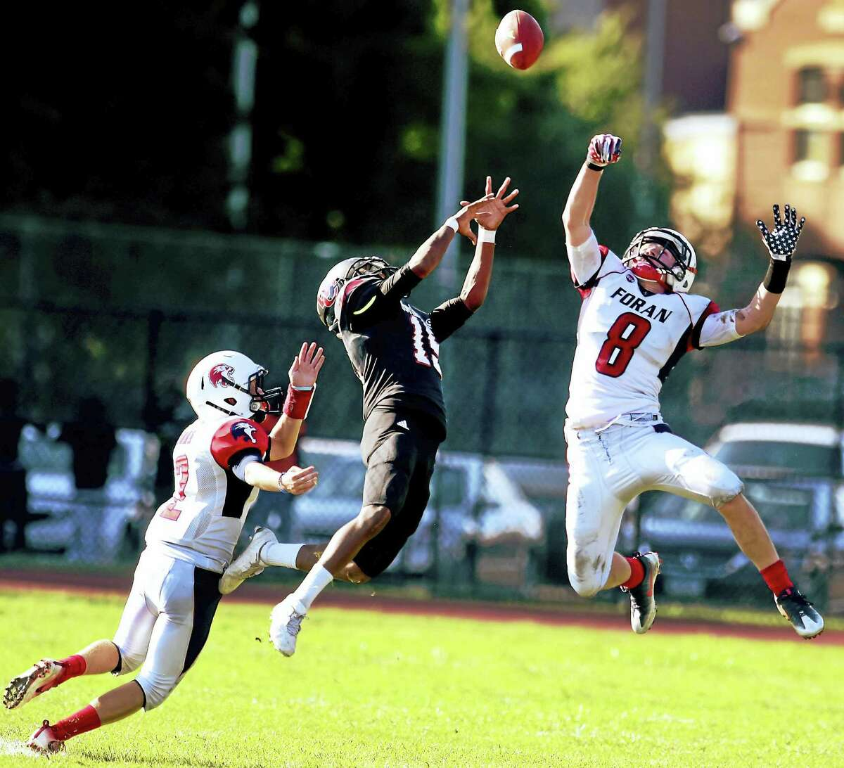 Defensive backs Mark Wooten, left, and Jared Hubler, right, of Foran High School double cover Dyante Howard of Wilbur Cross High School as they break up a pass play during second quarter football action at Cross H.S. in New Haven Friday afternoon, Sept. 9, 2016.