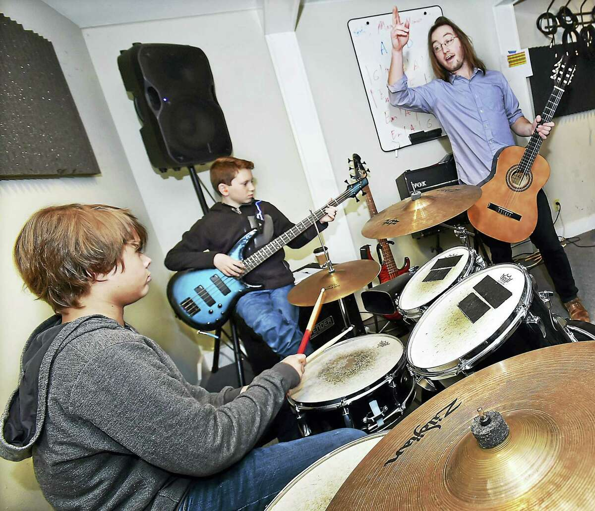 Music instructor Brendan Galvin, of Guilford, works with drummer James Pagano and Evan Landau, both 12 of Madison, during a band session at the Madison School of Rock Thursday.