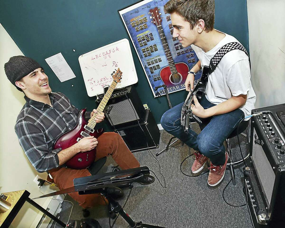 Music instructor Mike Molyneux, of West Haven, goves over lead guitar lines during a lesson to Nate Gariepy, 14, of Rocky Hill at the Madison School of Rock Thursday.