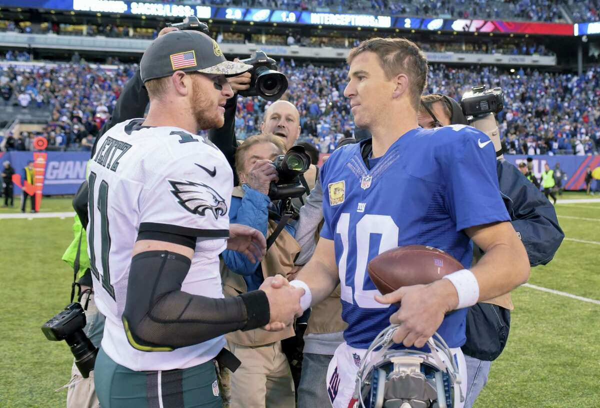 Eagles quarterback Carson Wentz, left, shakes hands with Giants quarterback Eli Manning after Sunday's game.