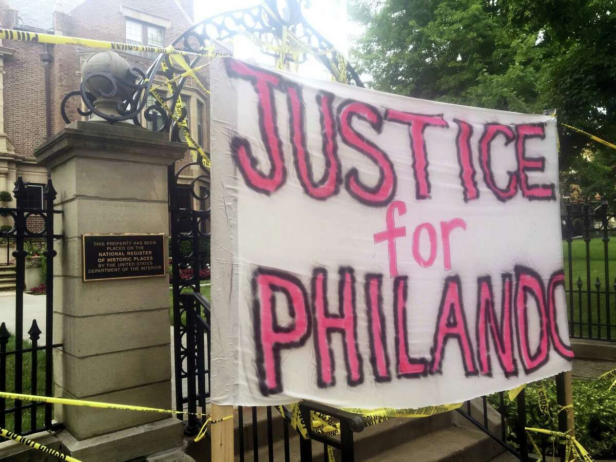A sign is hung outside the Minnesota Governor's Residence as about 200 people gathered in St. Paul, Thursday, July 7, 2016, protesting the fatal shooting of a man by a suburban police officer. Philando Castile was shot in a car Wednesday night in the largely middle-class St. Paul suburb of Falcon Heights. Police have said the incident began when an officer initiated a traffic stop in suburban Falcon Heights but have not further explained what led to the shooting.