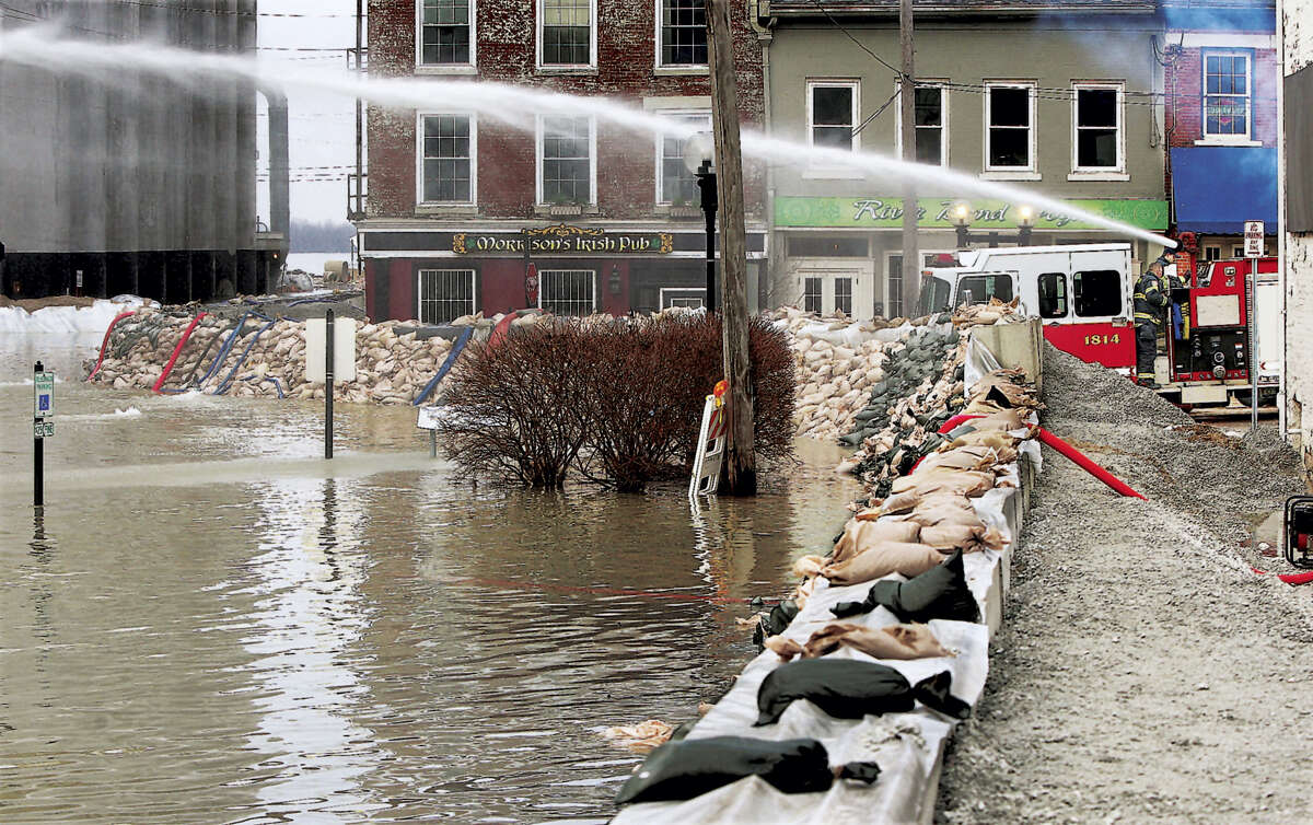 Firemen spray water towards water seepage under the city's makeshift flood levee in downtown Alton, Ill., Wednesday, Dec. 30, 2015. A rare winter flood threatened nearly two dozen federal levees in Missouri and Illinois on Wednesday as rivers rose, prompting evacuations in several places.