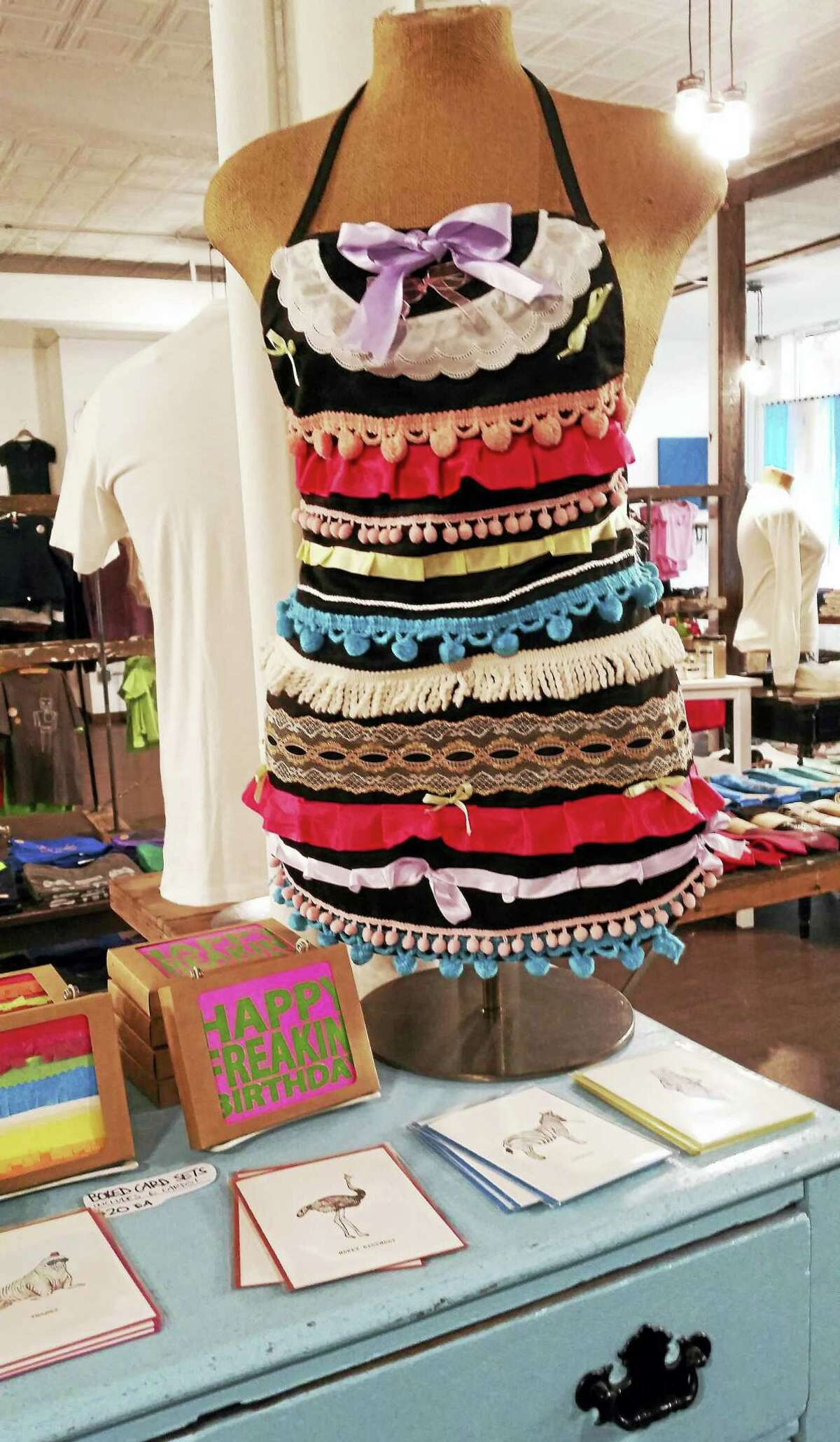 Colorful edging turns a run-of-the-mill apron into a dazzling minidress at Cinder + Salt, the new retail shop at 520 Main St., Middletown. Owner and creative director Rachel DeCavage hand draws and screen prints her upscale tee-shirt designs.