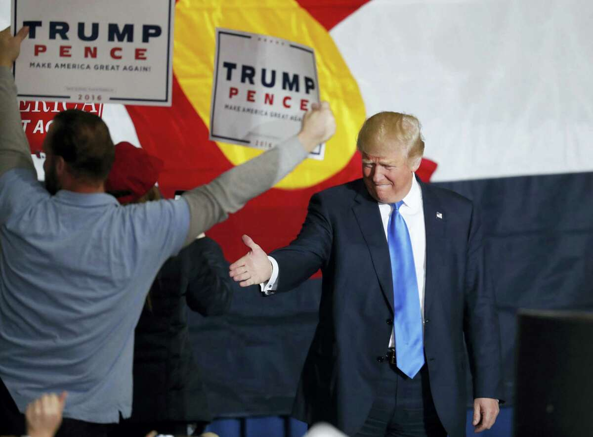 Republican presidential candidate, Donald Trump ,reaches out to shake hands with a supporter while taking the stage at a campaign rally late on Nov. 5, 201 in Denver.