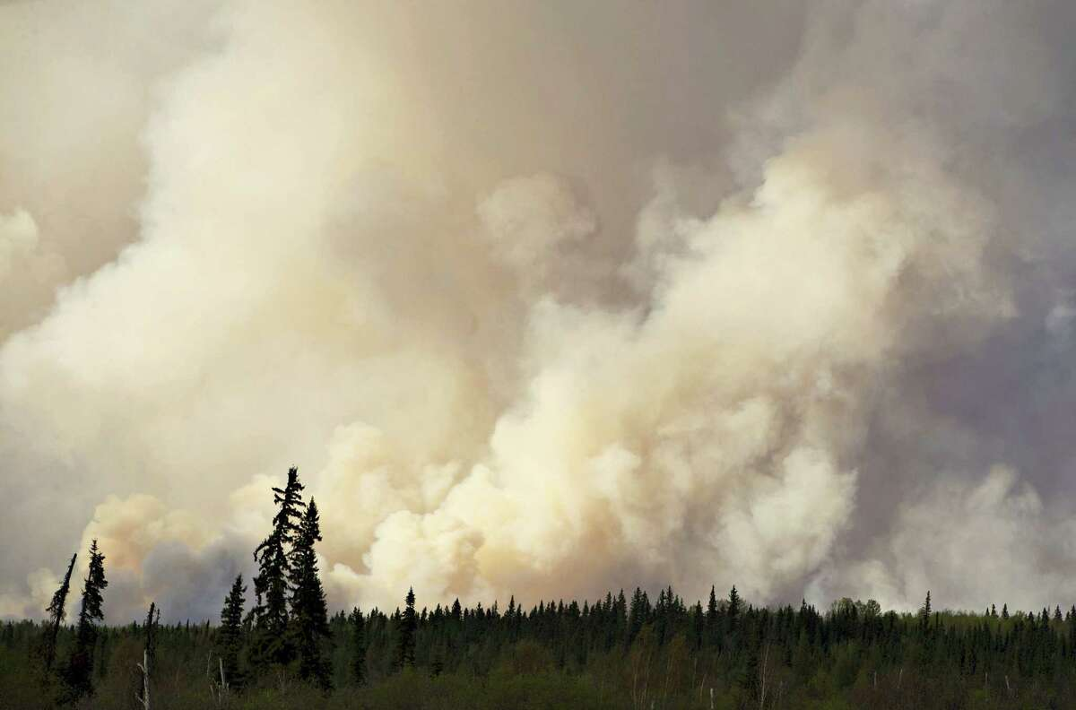 Smoke rises as a wildfire burns near Fort McMurray, Alberta, Thursday, May 5, 2016. An ever-changing, volatile situation is fraying the nerves of residents and officials alike as a massive wildfire continues to bear down on the Fort McMurray area of northern Alberta. The province of Alberta declared a state of emergency.
