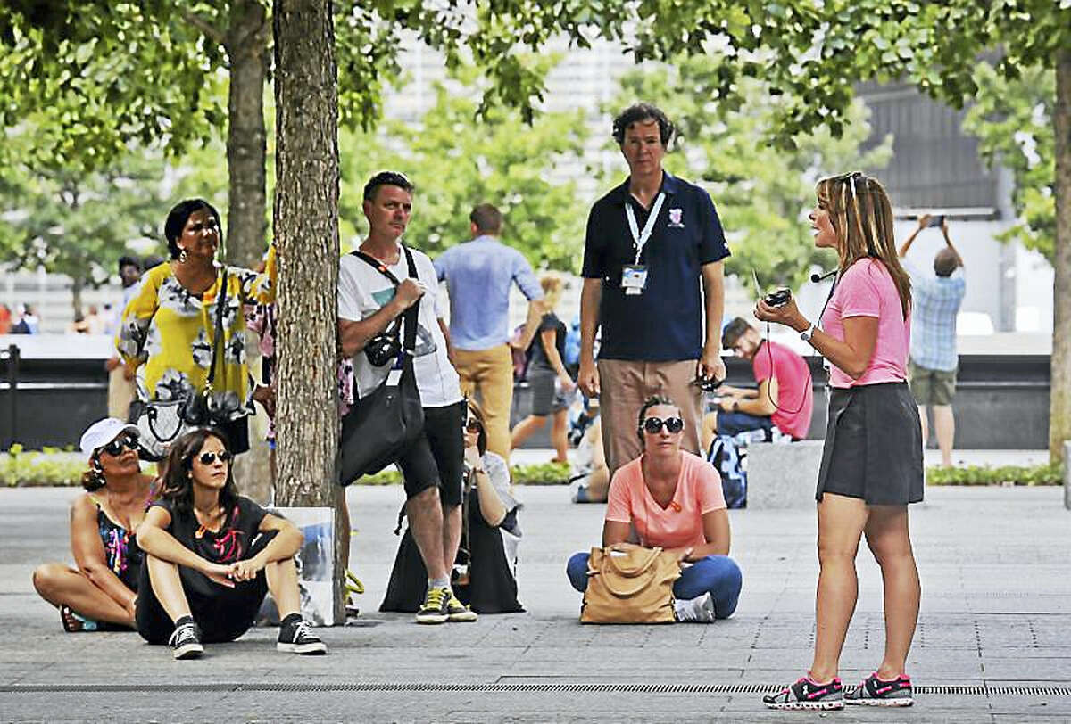 Jean Nebbia, far right, a schoolteacher from Oakland, N.J., talks with visitors to the Sept. 11 memorial site, Thursday Aug. 11, 2016, in New York. Nebbia serves as a volunteer tour guide, organized by the private nonprofit 9/11 Tribute Center, to tell tours about her brother Steven Schlag, a partner at Cantor Fitzgerald, who was killed in the Sept. 11 attacks on the World Trade Center.