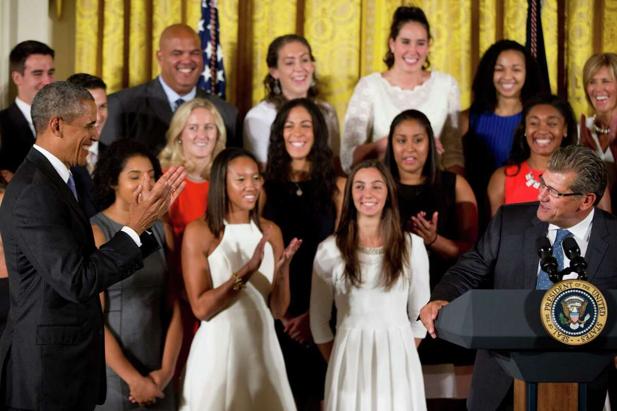 President Barack Obama reacts as UConn Huskies head Women's basketball coach Geno Auriemma, right, speaks in the East Room of the White House in Washington, Tuesday, Sept. 15, 2015, during a ceremony honoring the 2015 NCAA Womenís Basketball Champion University of Connecticut Huskies. (AP Photo/Andrew Harnik)