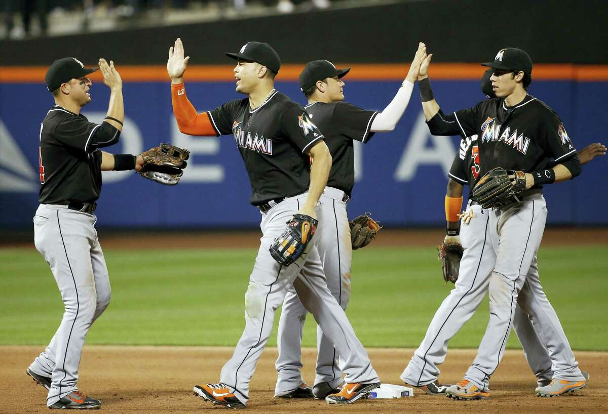 Miami Marlins right fielder Giancarlo Stanton, second from left, celebrates with teammates after the Marlins defeated the Mets 5-2 in a baseball game Tuesday, July 5, 2016, in New York. Stanton had a two-run home run in the game against the Mets. (AP Photo/Kathy Willens)