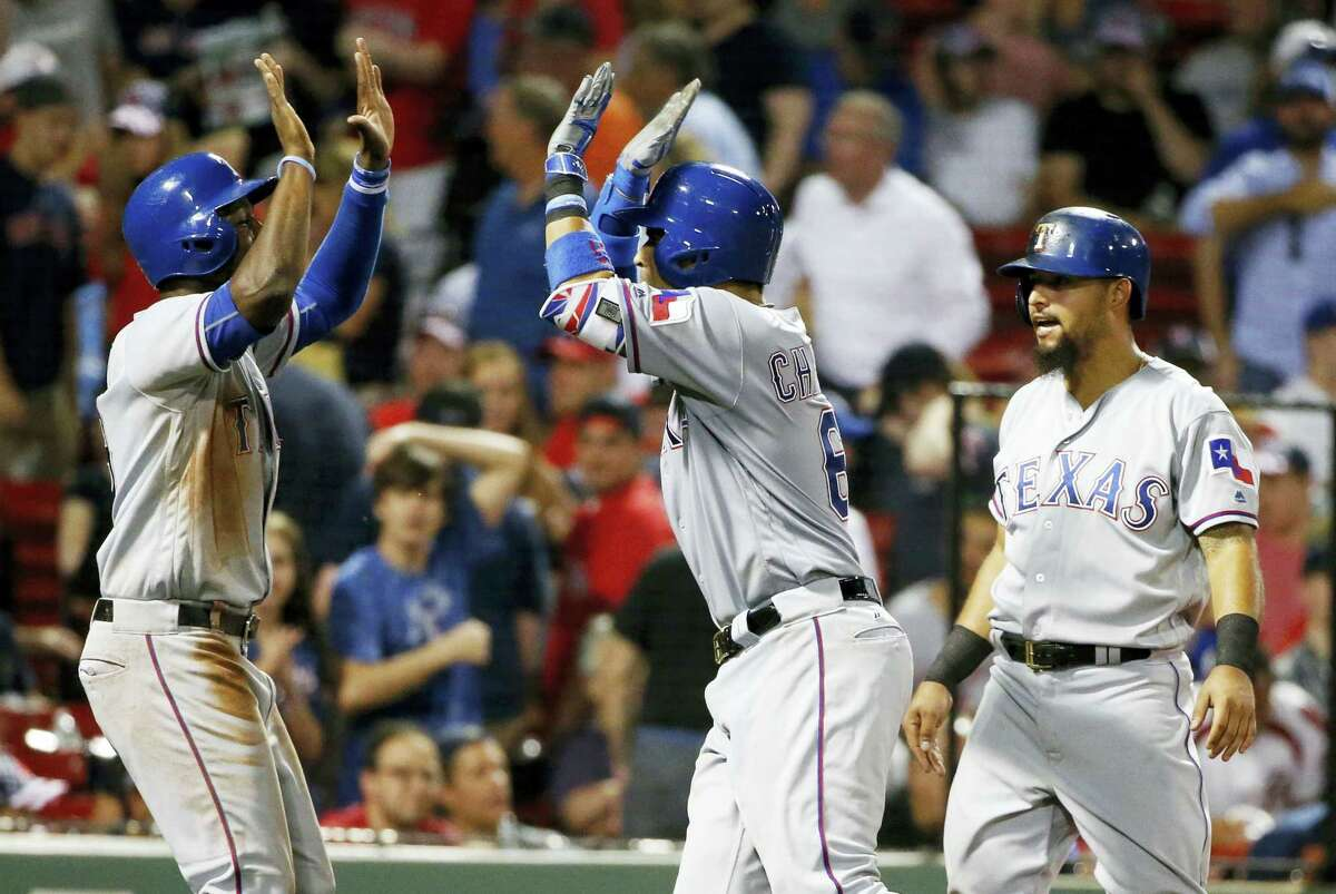 Texas Rangers' Robinson Chirinos, center, celebrates his three-run home run that also drove in Jurickson Profar, left, and Rougned Odor during the ninth inning against the Boston Red Sox. The Rangers won 7-2.