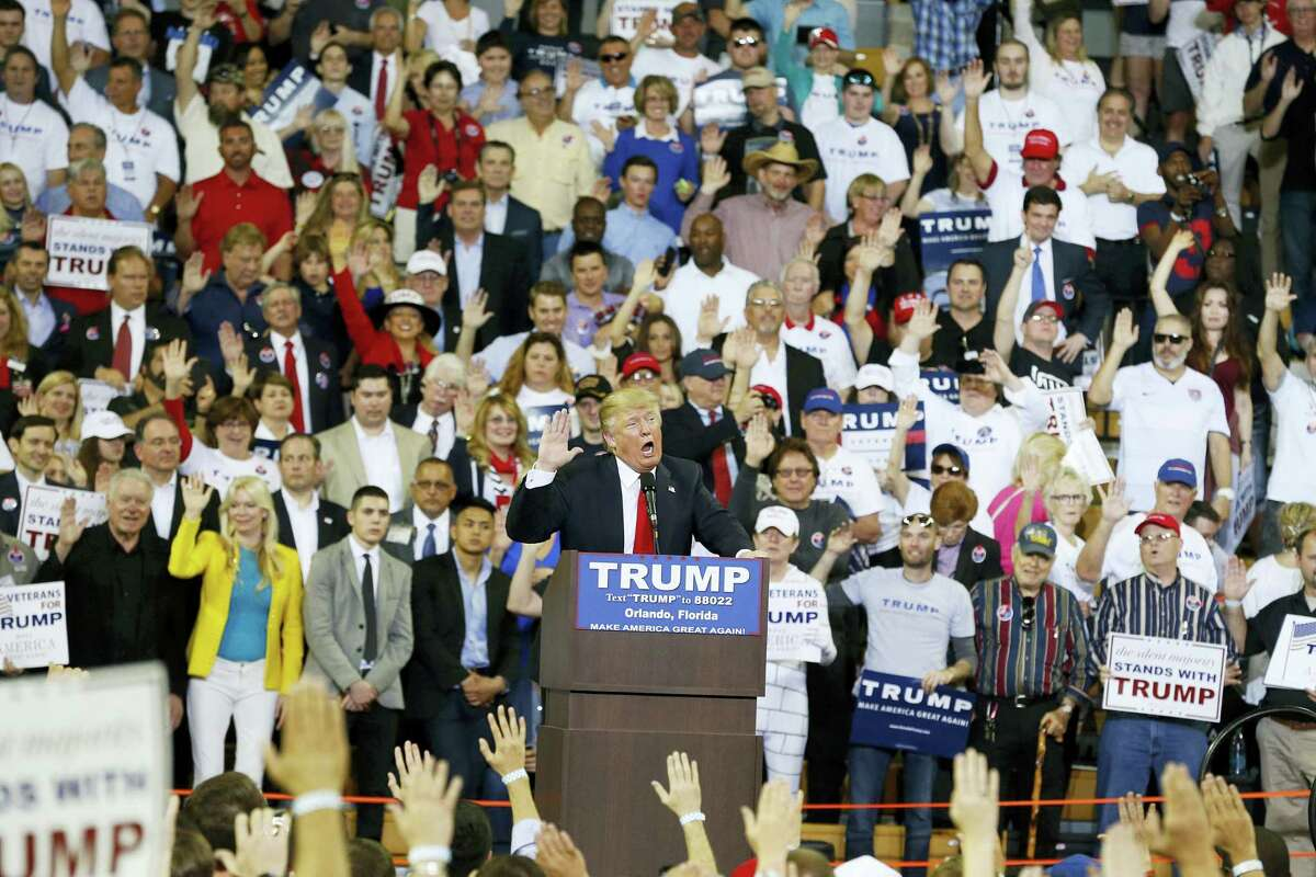 Republican presidential candidate Donald Trump speaks to the crowd asking them to take a pledge to promise to vote for him during a campaign rally, Saturday, March 5, 2016, in Orlando, Fla.