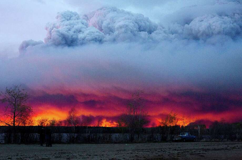 A wildfire moves towards the town of Anzac from Fort McMurray, Alberta., on Wednesday May 4, 2016. Alberta declared a state of emergency Wednesday as crews frantically held back wind-whipped wildfires. Unseasonably hot temperatures combined with dry conditions have transformed the boreal forest in much of Alberta into a tinder box. Photo: Jason Franson/The Canadian Press Via AP   / The Canadian Press