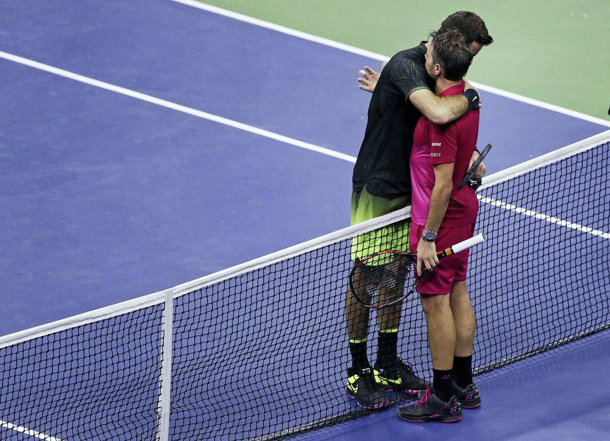 Juan Martin del Potro, left, of Argentina, is embraced by Stan Wawrinka, of Switzerland, after a quarterfinal at the U.S. Open tennis tournament, early Thursday, Sept. 8, 2016 in New York. Wawrinka won 7-6 (5), 4-6, 6-3, 6-2.