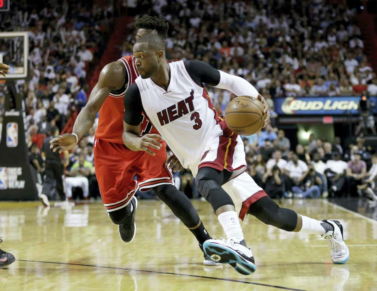In this April 7, 2016, file photo, Miami Heat guard Dwyane Wade (3) drives around Chicago Bulls guard Jimmy Butler. Wade has decided to leave the Heat after 13 seasons and sign with the Bulls.