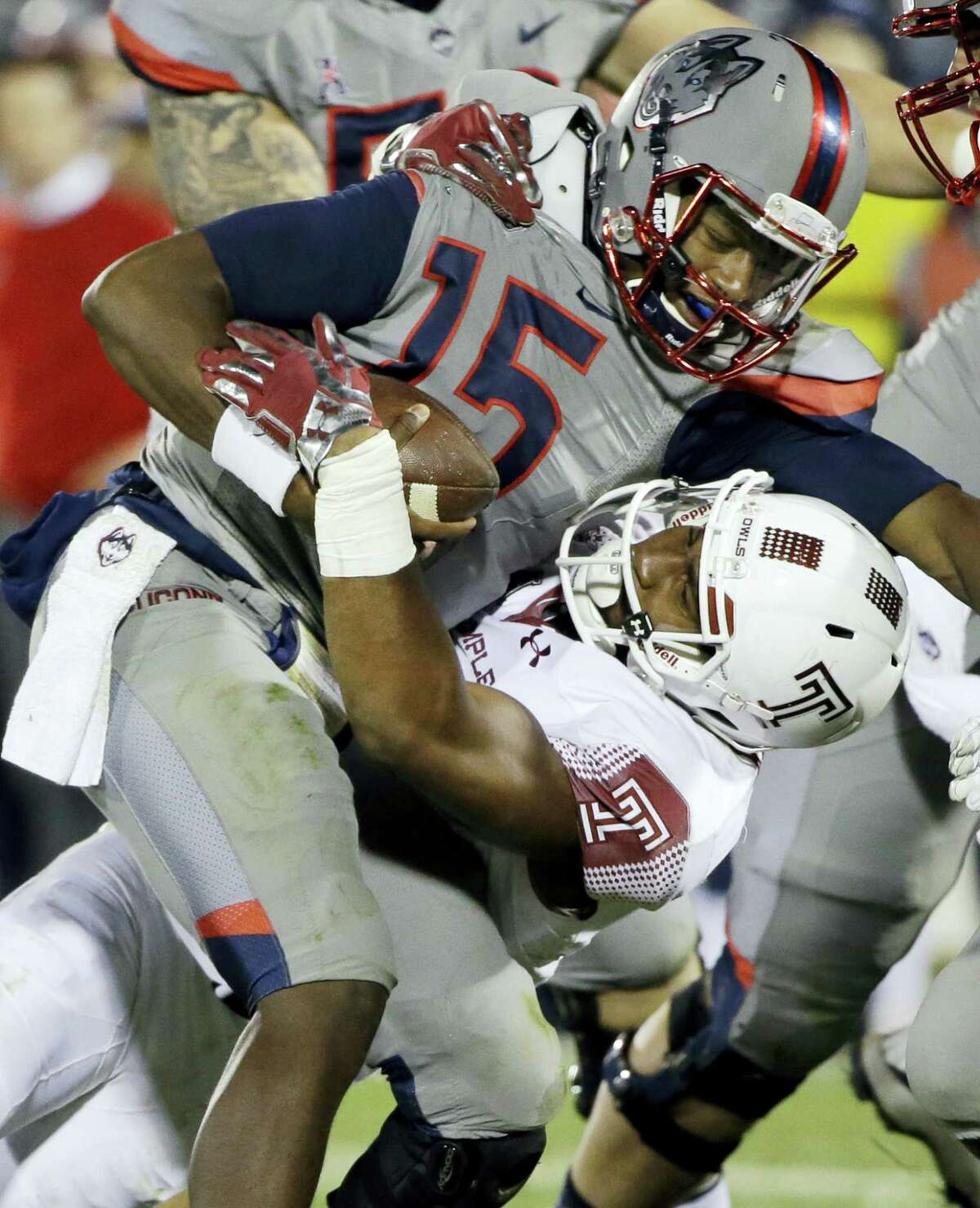 UConn quarterback Donovan Williams is brought down by Temple defensive lineman Haason Reddick during Friday night's game.