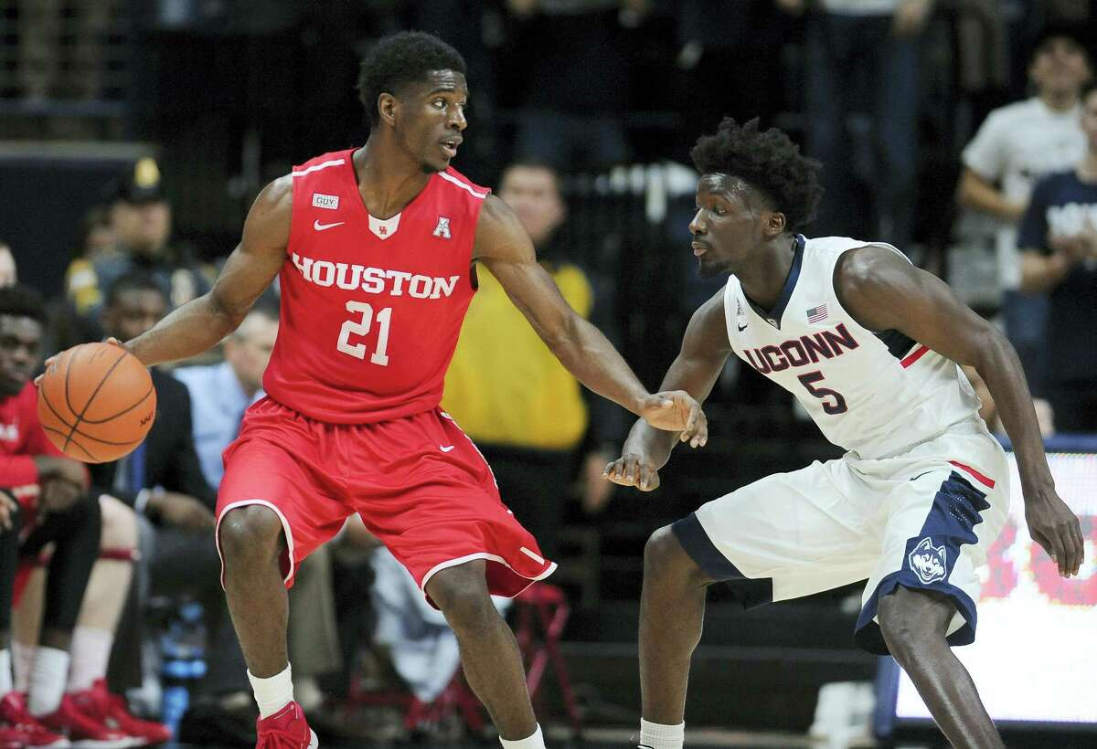 Houston's Damyean Dotson dribbles as Connecticut's Daniel Hamilton defends in the second half of an NCAA college basketball game, Sunday, Feb. 28, 2016, in Storrs, Conn. Houston won 75-68. (AP Photo/Jessica Hill)