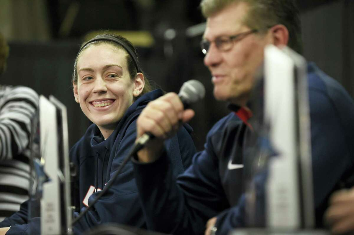 UConn's Breanna Stewart smiles as her coach Geno Auriemma talks about the upcoming American Athletic Conference tournament during a news conference Friday at the Mohegan Sun Arena.