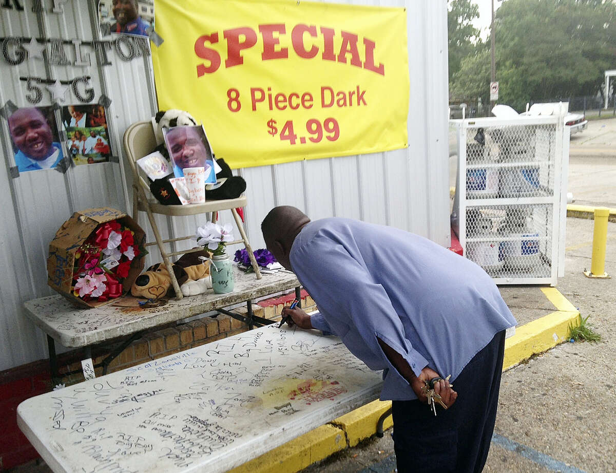"""Arthur Baines signs """"RIP Big Dogg"""" on a folding table that Alton Sterling used to sell homemade music CDs outside the convenience store, Wednesday, July 6, 2016, in Baton Rouge, La. A Louisiana police officer shot and killed Sterling, 37, a black man, during a confrontation outside the store, authorities said, prompting hundreds to protest at the site where the man died."""