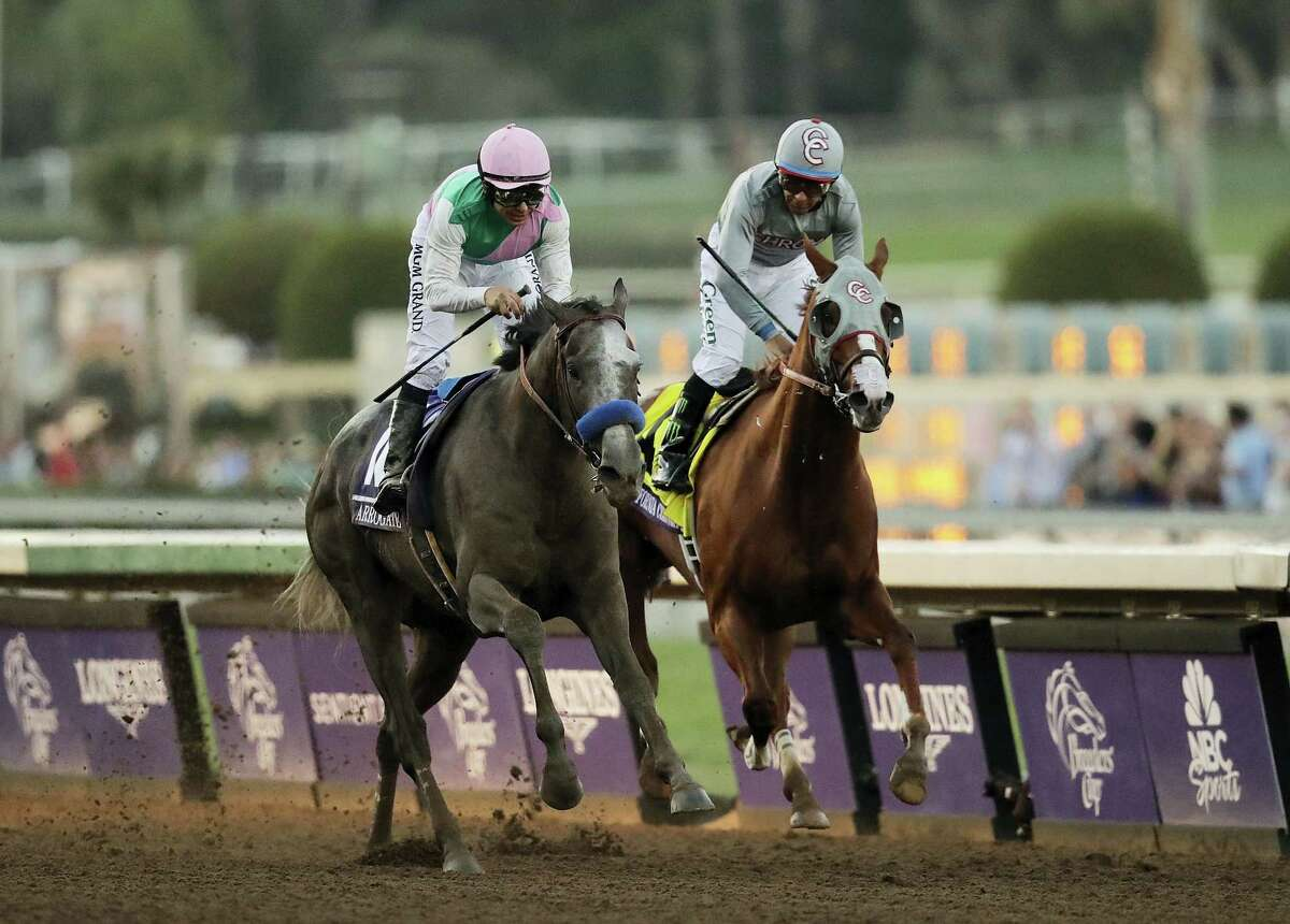 Arrogate, left, charges to the finish line to win the Breeders' Cup Classic against California Chrome on Saturday.