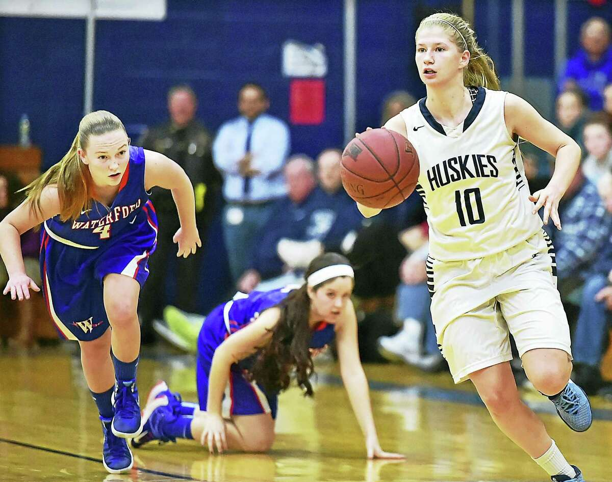 Morgan senior Sami Ashton drives past Waterford's Claire Hurley (4) and Vanessa Kobyluck (15) as the Huskies defeat the Waterford Lancers 50-36 in the second round of the CIAC Class M state tournament Thursday in Clinton.