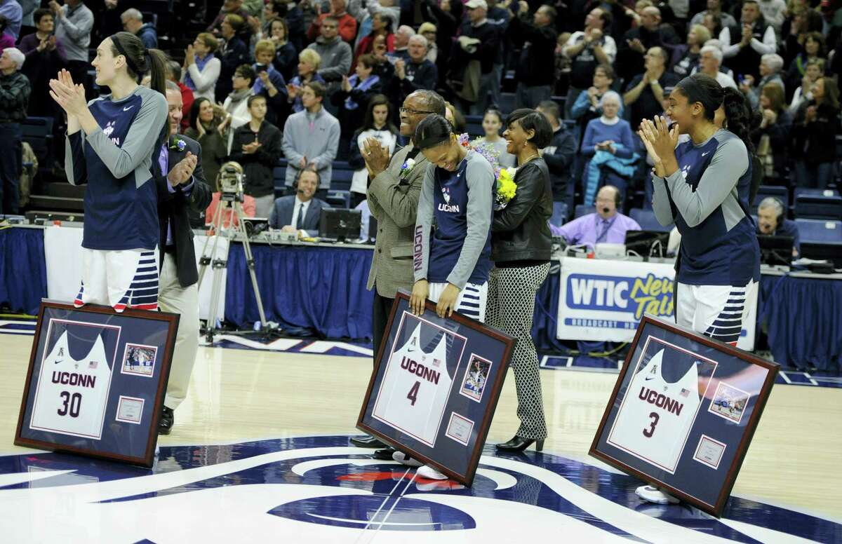 UConn's Moriah Jefferson, center, reacts as teammates Breanna Stewart, left, and Morgan Tuck, right, watch as her number is unveiled on the UConn Huskies of Honor wall at Gampel Pavilion.